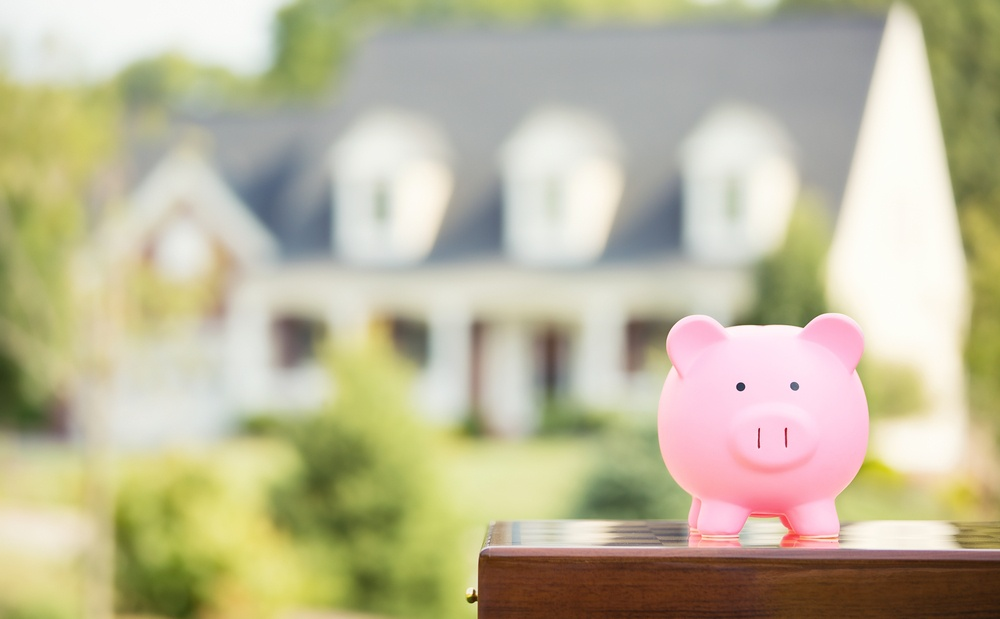 Real estate sale, home savings, loans market concept. Housing industry mortgage plan and residential tax saving strategy. Piggy bank isolated outside home on background. Focus on piggybank. Homeowner .jpeg